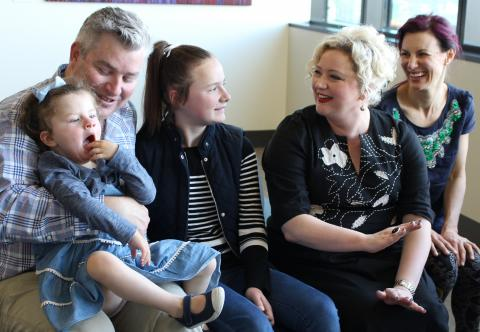Minister Hennessy with child patient Ginger and her family